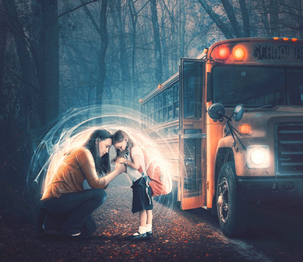 A mother and her child in prayer before getting on the school bus